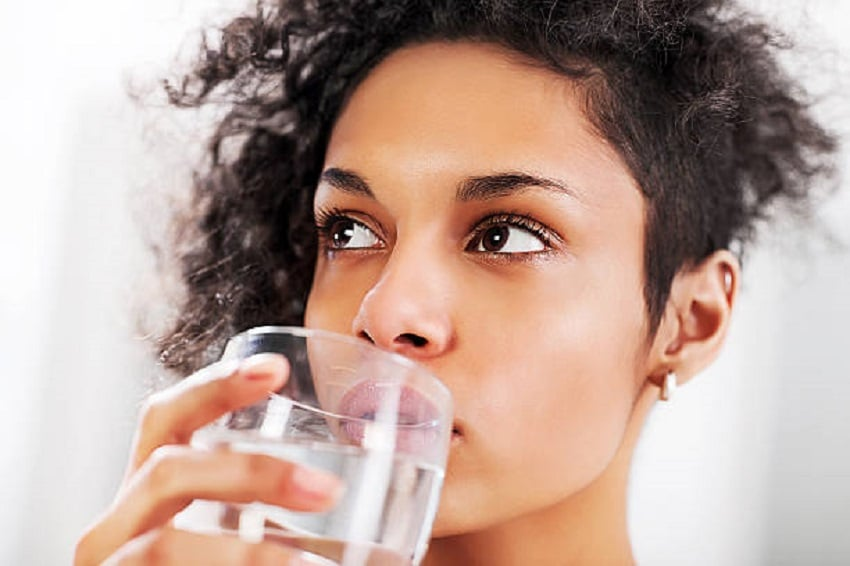 Close-up of African-American woman drinking water.