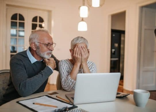old-couple-looking-at-laptop-in-dismay